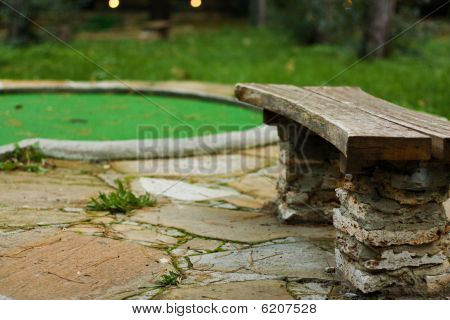 Outdoor green mini golf with bench near it