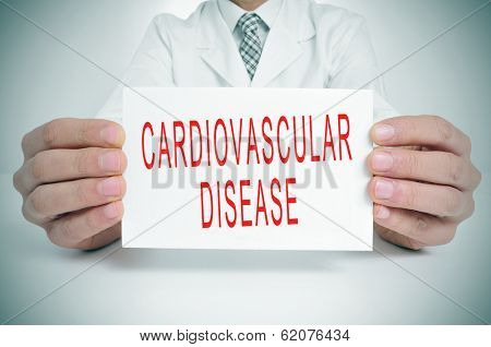a man wearing a white coat sitting in a desk holding a signboard with the text cardiovascular disease written in it