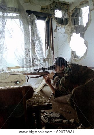 SARAJEVO, BOSNIA - MAY 16: A Bosnian Army sniper peers through his rifle scope at a Bosnian Serb military position in the besieged capital city of Sarajevo, Bosnia, on Sunday, May 16, 1993.