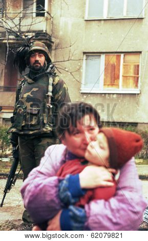 SARAJEVO, BOSNIA - MAR 18: Italian army troops, in Bosnia as part of the United Nations' UNPROFOR, watch over a refugee family in Sarajevo, Bosnia, on Monday, March 18, 1996.