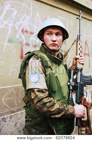 SARAJEVO, BOSNIA - FEB 16: A Ukrainian peacekeeper with the United Nations Protection Force (UNPROFOR), stands guard during an evacuation of refugees from Sarajevo, Bosnia, on Tuesday, February 16, 1993.