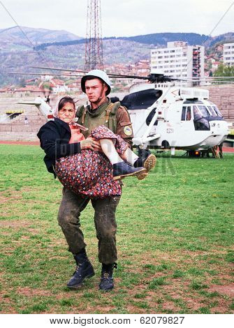 SARAJEVO, BOSNIA - APR 4: An Ukrainian soldier with the United Nations Protection Force (UNPROFOR) in Bosnia carries a woman wounded during the siege of Gorazde at a medical center in Sarajevo, Bosnia, on Monday, April 4, 1994