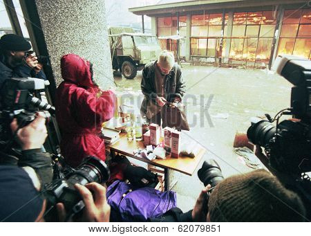 SARAJEVO, BOSNIA - MAR 18: Press photographers gather around a man buying supplies from a market stall engulfed in flames during the final days of siege in Sarajevo, Bosnia, on Monday, March 18, 1996