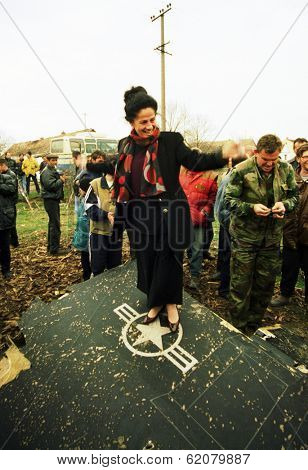BUDJANOVCI, BOSNIA - MAR 28: Serbian women dance atop the wing of an United States Air Force F-117A stealth fighter jet, shot down by Serb forces during a NATO bombing run in Budjanovci, Serbia, on Sunday, March 28, 1999.