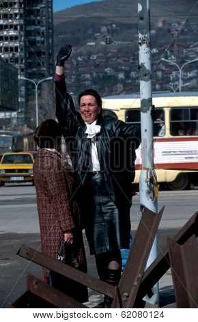 SARAJEVO, BOSNIA - MARCH 15: A Bosnian woman waves to friends across a no-man's land in Sarajevo. The city has been under siege by Bosnian Serb forces for nearly 3 years on Mar 15, 1996 in Sarajevo, Bosnia.