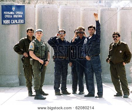SARAJEVO, BOSNIA - APR 24: Bosnian Serb paramilitaries wave at reporters after erecting a concrete wall in front of a French UNPROFOR checkpoint in Sarajevo, Bosnia, on Sunday, April 24, 1994.