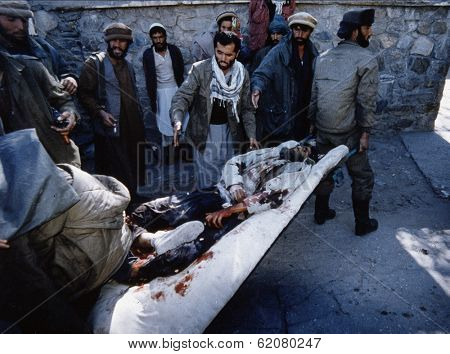 CHARIKAR, AFGHANISTAN - OCT 22: Mujaheddin fighters rush a Northern Alliance soldier to a hospital in Charikar, Afghanistan, on Wednesday, October 22, 1996.