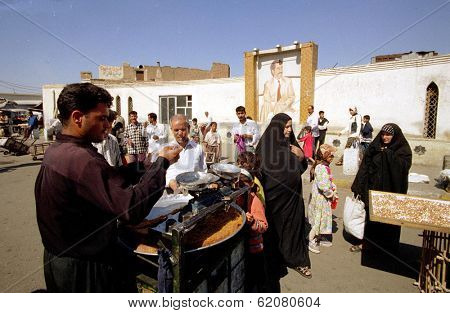 BAGHDAD, IRAQ - MARCH 14:  Iraqis shop for sweet cakes at an outdoor market in a predominantly Shiite Muslim neighborhood in Baghdad on March 14, 1999 in Baghdad, Iraq.