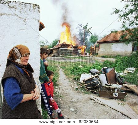 VUCITRN, KOSOVO - JUNE 26: Recently returned ethnic Albanians watch as the home of a Serb family burn to the ground by the Kosovo Liberation Army as an act of revenge. in Vucitrn, Kosovo, on Saturday, June 26, 1999.