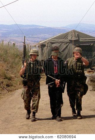 GNIJLANE, KOSOVO, 22 JUNE 1999 - United States Marines with the 26th Marine Expeditionary Unit exercise a  Kosovar Serb sniper captured after a firefight with the Marines.