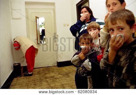 GYOR, HUNGARY - OCTOBER 14:  Kosovar Albanians at a Hungarian refugee center, some as young as eight, cover their noses while a Kosovar Albanian woman at rear convulses with stomach pains on October 14, 1998 in Gyor, Hungary
