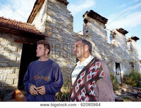 BANJA, KOSOVO - OCTOBER 4: Arben Samadraxha, 19, left, and his father Haxhi, 46, outside their family's destroyed home in Kosovo's war-stricken Drenica region on October 4, 1998 in Banja, Kosovo