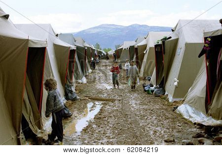 KUKES, ALBANIA, 19 APRIL 1999 -- A river of mud flows between rows of tents housing refugees at an Italian government-operated camp for Kosovar Albanians.