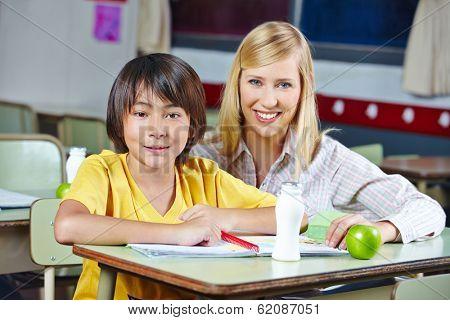 Teacher coaching Japanese student in elementary school