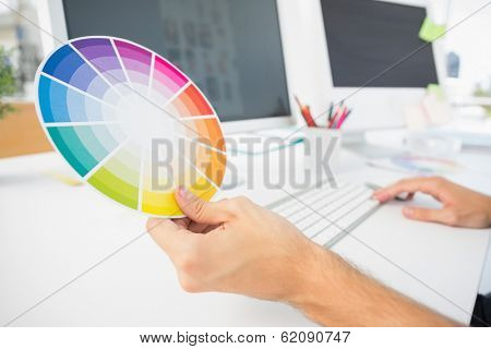 Closeup of hand holding color wheel while using computer at desk