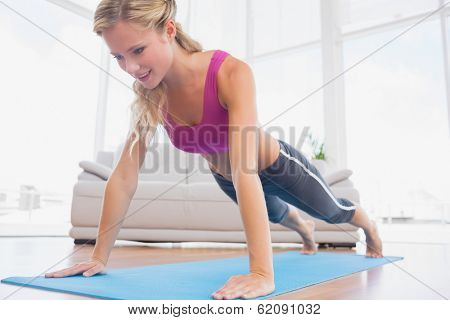 Strong blonde in plank position on exercise mat at home in the living room