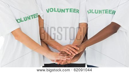 Team of volunteers putting hands together on white background