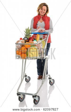 A woman with a supermarket trolley full of fresh food checking her shopping list, isolated on a white background.