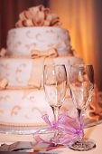 foto of three tier  - Three tiered wedding cake and champagne glasses on a table - JPG