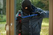 stock photo of sneak  - A burglar striving to open a window to a house - JPG