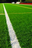 Green sports field with artificial grass and racetrack