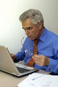 picture of oddities  - A businessman looks at his laptop computer as though it - JPG