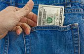 stock photo of twenty dollars  - A person pulling a twenty dollar bill out of a denim blue jean back pocket - JPG