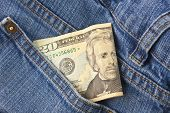 image of twenty dollars  - A twenty dollar bill sticking out the front pocket of denim blue jeans - JPG