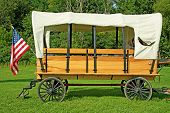 picture of covered wagon  - Horse drawn covered wagon with an American fkag - JPG