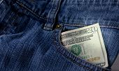 stock photo of twenty dollar bill  - A twenty dollar bill sticking out the front pocket of denim blue jeans - JPG