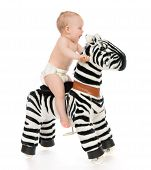 image of baby cowboy  - Cute child baby toddler sit and ride big zebra horse toy on a white background - JPG