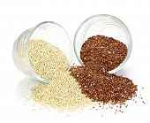 Red and white quinoa grain in glass bowls on white background