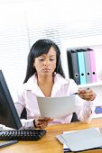 Young black business woman reading document at desk in office