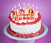 pic of uncut  - Birthday cake with burning candles on a plate on pink background - JPG