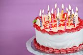 foto of uncut  - Birthday cake with burning candles on a plate on pink background - JPG