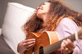 Beautiful Afroamerican Girl Having Fun Playing Guitar