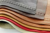 stock photo of stitches  - Natural leather upholstery samples with stitching in various colors - JPG