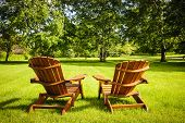 stock photo of lawn chair  - Two wooden adirondack chairs on lush green lawn with trees - JPG