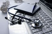 Stethoscope on keyboard and notepad with pen isolated