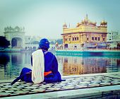 stock photo of harmandir sahib  - Vintage retro hipster style travel image of unidentifiable Seekh Nihang warrior meditating at Sikh temple Harmandir Sahib - JPG