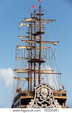 Masts and sails of huge sailing boat against the background of blue sk