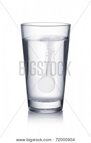 Glass with effervescent tablet in water with bubbles on white  background