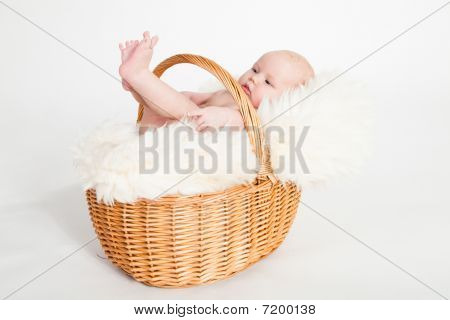 A beautiful baby girl with cute facial expression lying in a basket