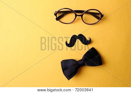 Glasses, mustache and bow tie forming man face on yellow background
