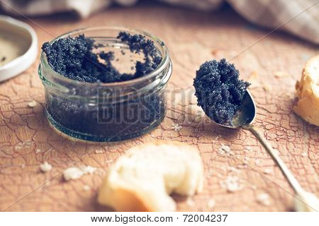black caviar in jar and in spoon