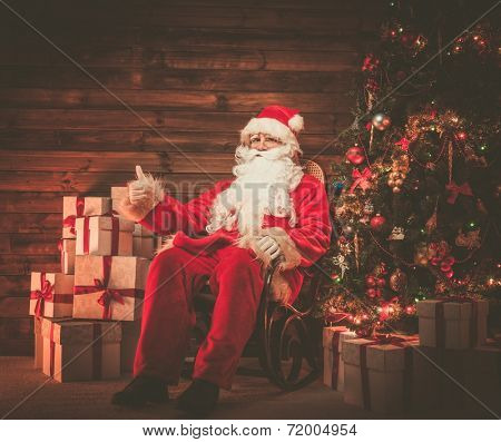 Santa Claus sitting on rocking chair with thumb up in wooden home interior with gift boxes around him