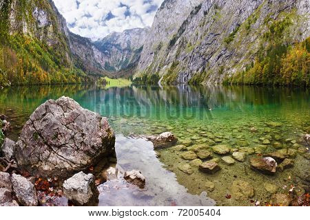 Magic reflection in German lake Koenigssee. Cloudy day on the lake. Clouds and mountains reflected in the emerald surface of the water