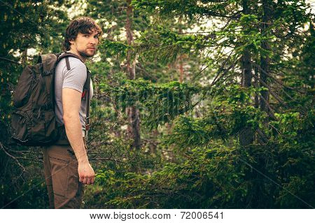 Young Man Walking In Forest With Backpack Hiking Lifestyle And Outdoor Recreation Concept