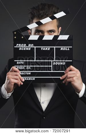 Studio portrait of a young man with a suit and holding a clapboard