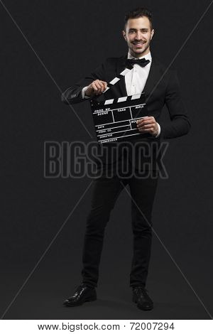 Studio portrait of a fashion young man wearing a suit and holding a clapboard